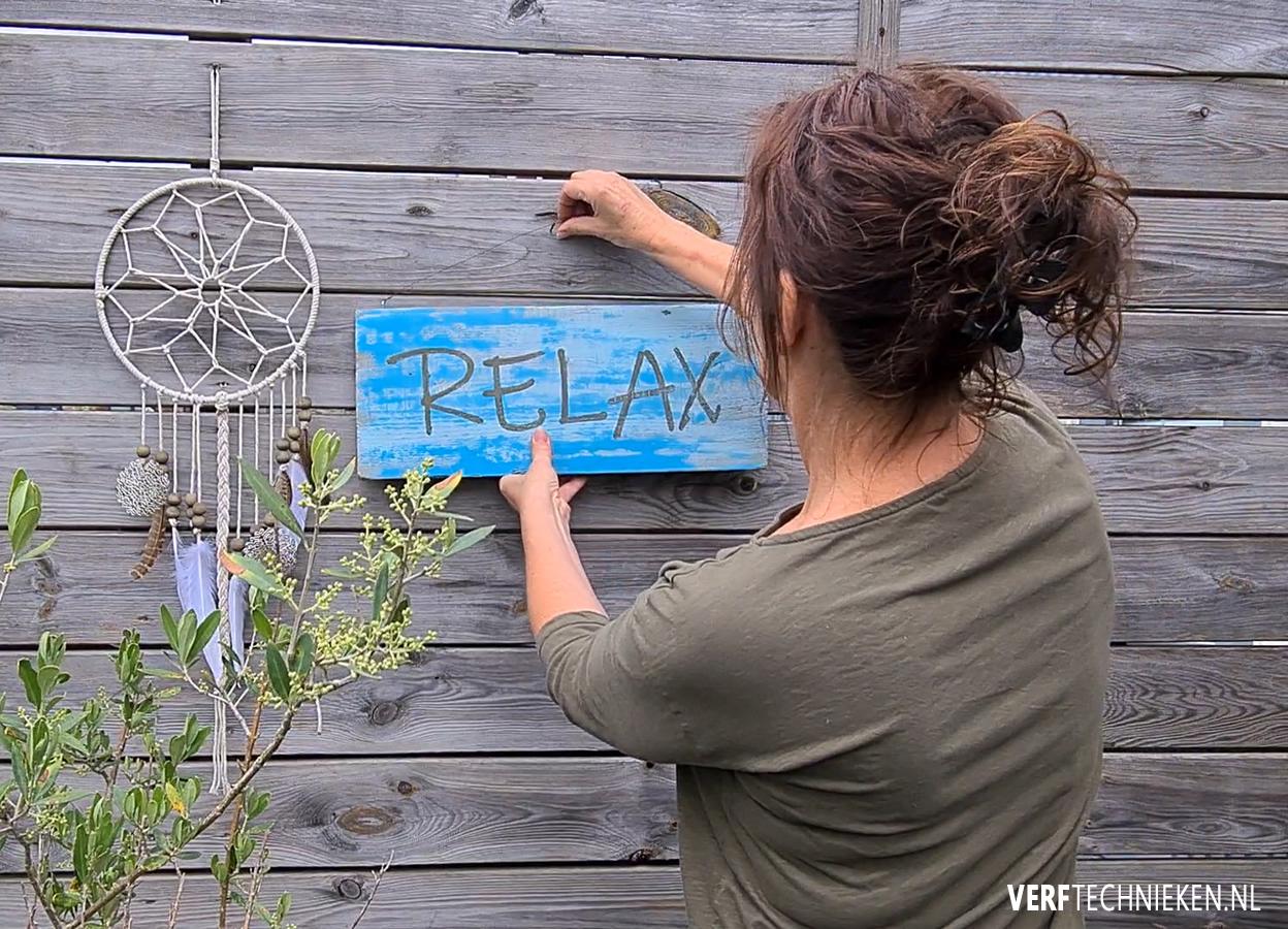 Tekstbord ophangen aan een muur of schutting